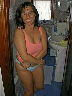 Brunette mature woman in panties about to take off her peach tanktop.jpg